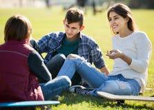 Adolescentes que cuelgan hacia fuera al aire libre y que discuten algo Imagenes de archivo