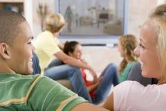 Adolescentes que cuelgan hacia fuera delante de la televisión Fotos de archivo libres de regalías