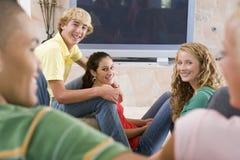 Adolescentes que cuelgan hacia fuera delante de la televisión Foto de archivo