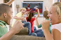 Adolescentes que cuelgan hacia fuera delante de la televisión Fotos de archivo