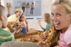 Adolescentes que cuelgan hacia fuera delante de la televisión Imágenes de archivo libres de regalías
