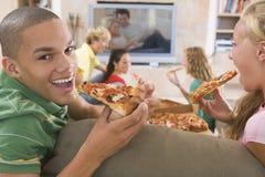 Adolescentes que cuelgan hacia fuera delante de la televisión Imagen de archivo libre de regalías