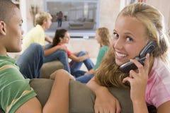 Adolescentes que cuelgan hacia fuera delante de la televisión Imagenes de archivo
