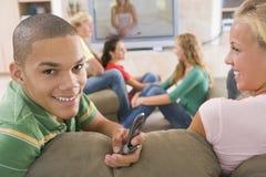 Adolescentes que cuelgan hacia fuera delante de la televisión Fotografía de archivo libre de regalías