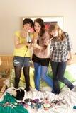 Adolescentes que cuelgan hacia fuera en dormitorio desordenado Imagenes de archivo