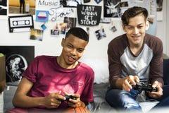 Adolescentes que cuelgan hacia fuera en un dormitorio que juega a los videojuegos juntos Imagen de archivo
