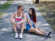 Adolescentes que datam em um parque, em uma menina bonita e em um companheiro sentando-se em um longboard em um fundo borrado nat foto de stock royalty free
