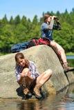 Adolescentes que descansam e que birdwatching pelo lago fotografia de stock