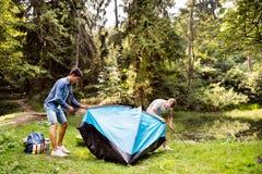 Adolescentes que echan una tienda en el lago en bosque Imagen de archivo libre de regalías