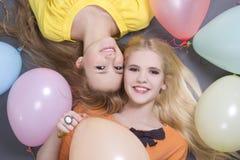 Adolescentes que encontram-se com balões coloridos Foto de Stock