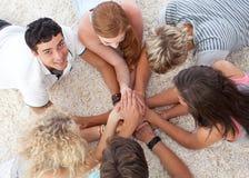 Adolescentes que encontram-se na terra com mãos junto Fotos de Stock