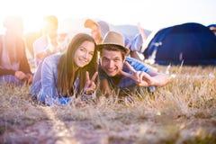 Adolescentes que encontram-se na terra na frente das barracas Fotografia de Stock Royalty Free