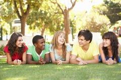Adolescentes que encontram-se nos estômagos no parque Imagens de Stock