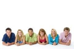 Adolescentes que encontram-se para baixo em uma fileira Foto de Stock Royalty Free
