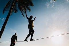 Adolescentes que equilibran en slackline con la opinión del cielo Foto de archivo