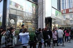 Adolescentes que esperan en línea para incorporar la línea café de los amigos y para hacer compras en Shangai Imagenes de archivo