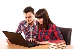 Adolescentes que estudian así como un ordenador portátil Fotografía de archivo