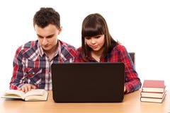 Adolescentes que estudian así como un ordenador portátil Imágenes de archivo libres de regalías