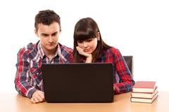 Adolescentes que estudian así como un ordenador portátil Fotos de archivo