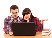 Adolescentes que estudian así como un ordenador portátil Fotos de archivo libres de regalías