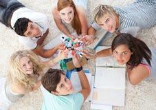 Adolescentes que estudian ciencia en el suelo Fotos de archivo libres de regalías