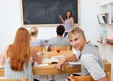 Adolescentes que estudian junto en una clase Foto de archivo libre de regalías