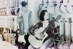 Adolescentes que examinan las guitarras acústicas eléctricas y Fotografía de archivo libre de regalías