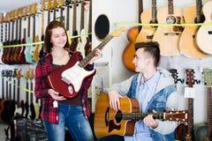 Adolescentes que examinan las guitarras acústicas eléctricas y Fotos de archivo