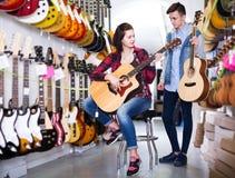 Adolescentes que examinan las guitarras en tienda Fotografía de archivo