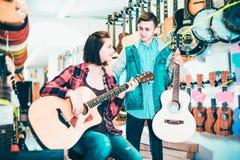 Adolescentes que examinan las guitarras en tienda Foto de archivo