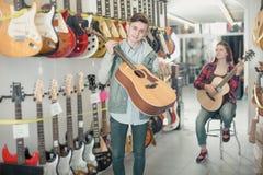 Adolescentes que examinan las guitarras en tienda Foto de archivo libre de regalías