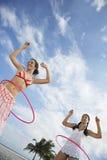 Adolescentes que giran los aros de Hula en la playa Imagen de archivo libre de regalías