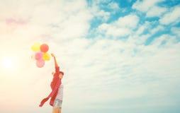 Adolescentes que guardam balões coloridos no céu e na manutenção programada brilhantes Imagens de Stock Royalty Free