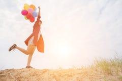 Adolescentes que guardam balões coloridos no céu e na manutenção programada brilhantes Fotos de Stock Royalty Free