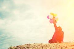 Adolescentes que guardam balões coloridos no céu e na manutenção programada brilhantes Foto de Stock Royalty Free