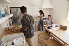 Adolescentes que hacen el almuerzo y que estudian junto en una cocina Imagen de archivo libre de regalías
