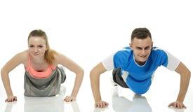 Adolescentes que hacen flexiones de brazos Imagen de archivo