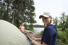 Adolescentes que hacen una pausa la tienda cerca del lago Fotografía de archivo