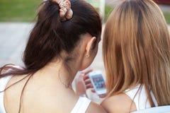 Adolescentes que hojean las fotos en el teléfono móvil Foto de archivo
