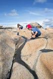 Adolescentes que jogam com o córrego na rocha Fotografia de Stock