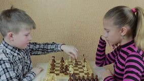 Adolescentes que juegan a ajedrez en la sala de estar almacen de metraje de vídeo