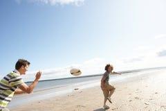 Adolescentes que juegan al rugbi en la playa junto Fotos de archivo