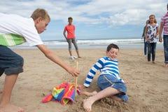 Adolescentes que juegan a béisbol en la playa Fotos de archivo libres de regalías