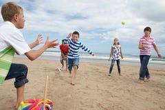Adolescentes que juegan a béisbol en la playa Imagenes de archivo