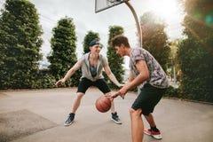 Adolescentes que juegan a baloncesto en corte al aire libre Foto de archivo