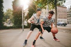 Adolescentes que juegan a baloncesto en corte al aire libre Imagen de archivo libre de regalías