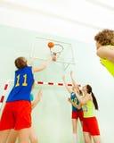 Adolescentes que juegan a baloncesto en pasillo de deportes Fotos de archivo libres de regalías