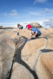 Adolescentes que juegan con la corriente en la roca Fotografía de archivo