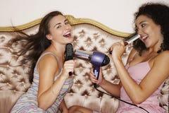 Adolescentes que juegan con los cepillos y el secador de pelo Imagenes de archivo