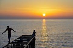 Adolescentes que juegan en el embarcadero en puesta del sol Foto de archivo